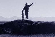 child and woman standing on a rock in the ocean ponting to the next rock